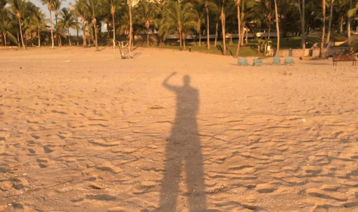 woman's shadow on sandy beach