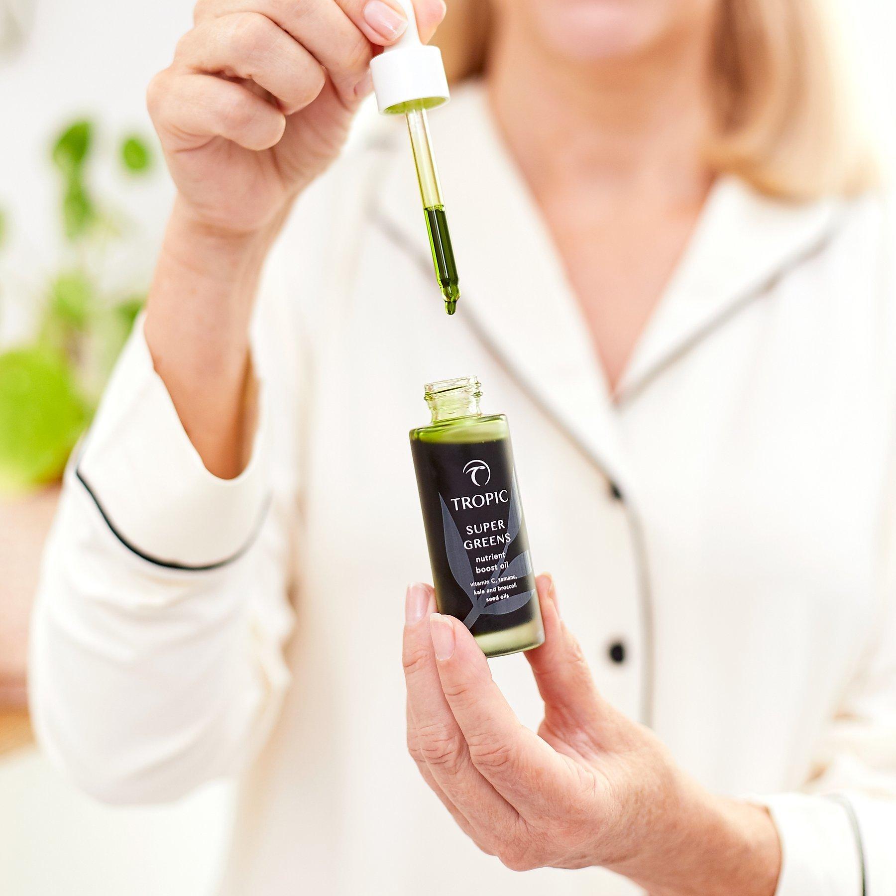 woman holding bottle of super greens skin serum