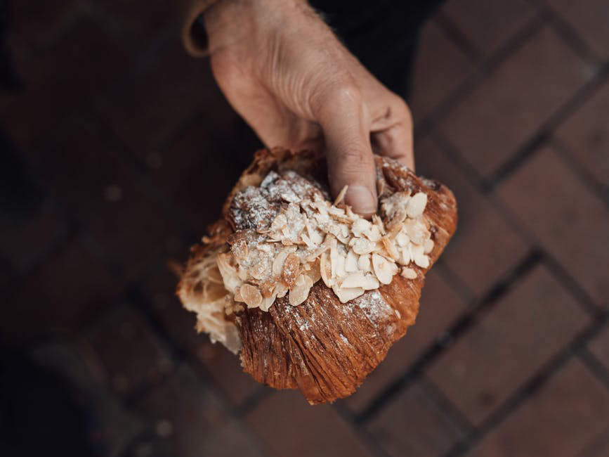 holding a croissant on the go